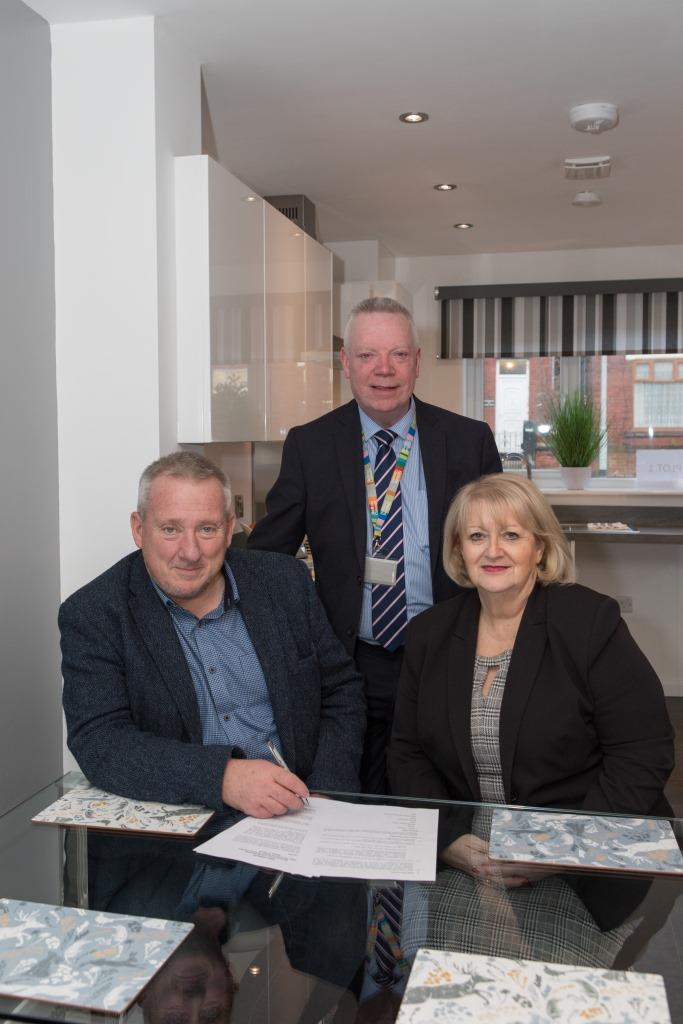 Picture of Jon Lord, Martin Donaghy and Linda Thomas in the kitchen of the show house at Park Grove, signing the memorandum of understanding