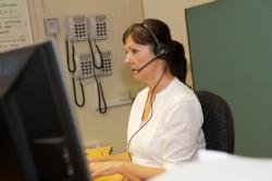 Female careline operator sitting at desk with headset
