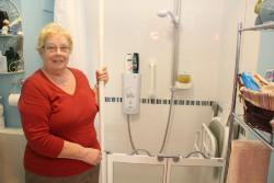 older lady standing next to walk in shower