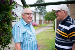 Two older men chatting in a garden